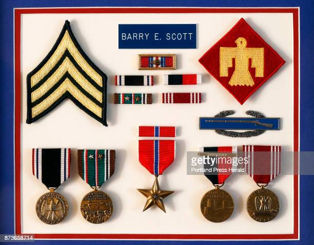 A matted frame holds Army veteran Barry Scott's various medals ribbions and patches from his service as a private first class in World War II The...