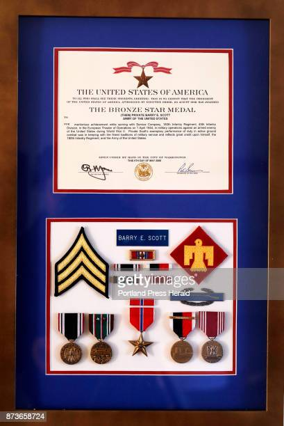 A matted frame holds Army veteran Barry Scott's various medals ribbions and patches from his service as a private first class in World War II and a...