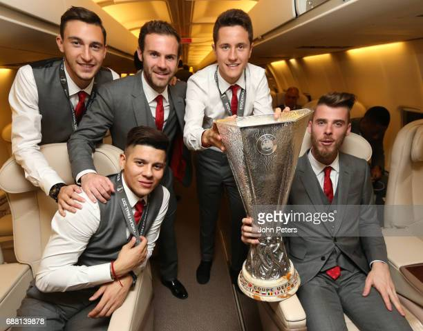 Matteo Darmian Marcos Rojo Juan Mata Ander Herrera and David de Gea of Manchester United celebrate with the Europa League trophy on the plane home...