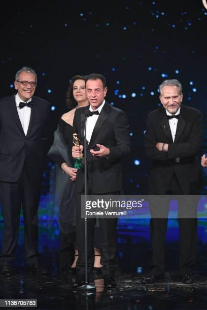 Matteo Garrone Ugo Citi and Massimo Gaudioso receive the Best Original Script award from Stefania Sandrelli during the 64 David Di Donatello Award...
