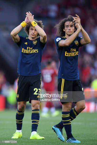 Matteo Guendouzi and David Luiz of Arsenal applaud the fans following their sides defeat in the Premier League match between Liverpool FC and Arsenal...