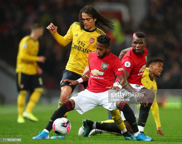 Matteo Guendouzi of Arsenal battles for possession with Fred of Manchester United and Paul Pogba of Manchester United during the Premier League match...