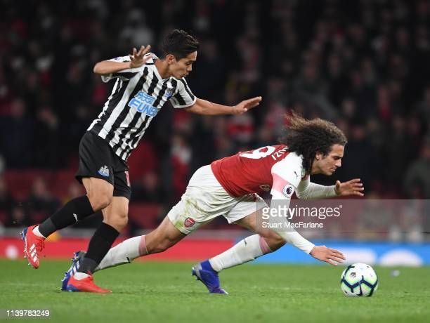 Matteo Guendouzi of Arsenal is challenged by Yoshinori Muto of Newcastle during the Premier League match between Arsenal FC and Newcastle United at...