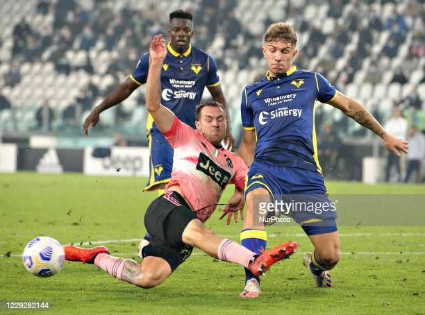 Matteo Lovato of Hellas Verona FC competes for the ball with Aaron Ramsey of Juventus during the Serie A match between Juventus and Hellas Verona FC...