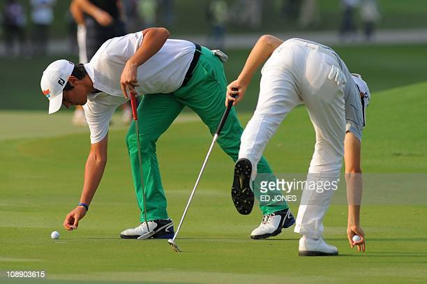 Matteo Manassero of Italy and Gregory Bourdy of France lean to collect their balls on the 17th green during the final day of the UBS Hong Kong Open...