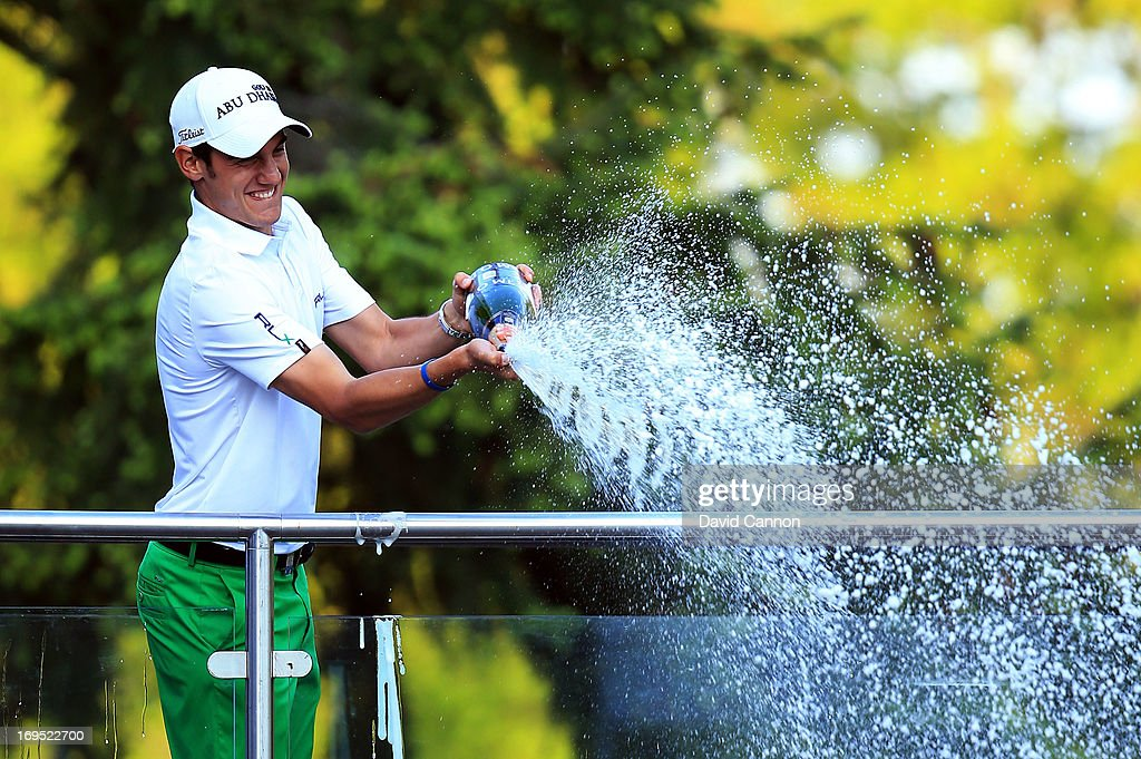 Matteo Manassero of Italy celebrates victory with a bottle of champagne behind the eighteenth green following the final round of the BMW PGA Championship on the West Course at Wentworth on May 26, 2013 in Virginia Water, England.