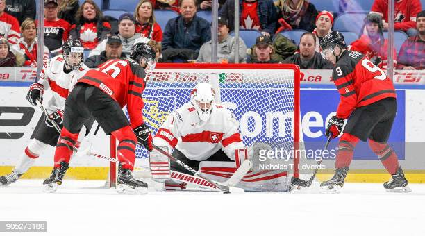 Matteo Ritz of Switzerland defends his net against Taylor Raddysh and Dillon Dubé of Canada during the second period of play in the Quarterfinal IIHF...