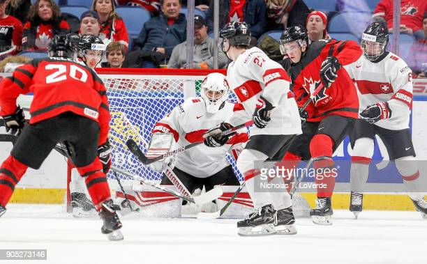 Matteo Ritz of Switzerland makes a save as Drake Batherson of Canada looks for the rebound during the second period of play in the Quarterfinal IIHF...
