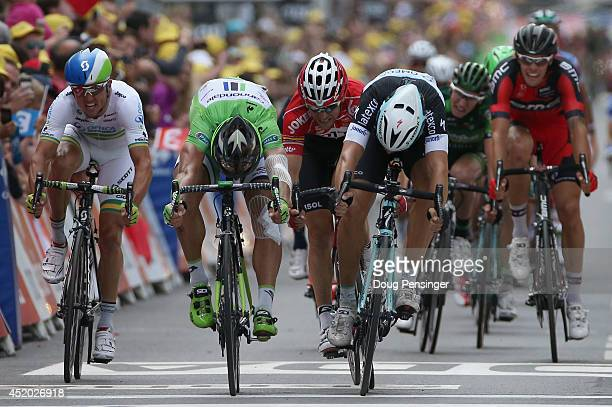 Matteo Trentin of Italy and the Omega Pharma - Quick-Step Cycling Team throws his bike across the line to beat Peter Sagan of Slovakia and Cannondale...
