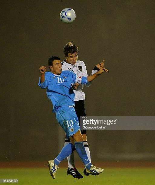 Matteo Vitaioli of San Marino and Holger Badstuber of Germany jump for a header during the UEFA Under 21 Championship match between San Marino and...