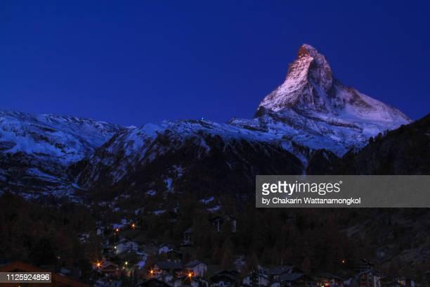 matterhorn (zermatt, switzerland) - early sunlight touching the tip of matterhorn with twilight sky. - pinnacle peak stock-fotos und bilder
