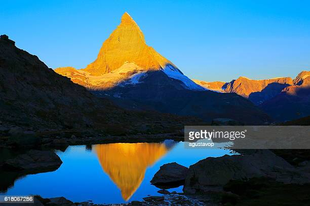Matterhorn mirrored lake reflection, peaceful sunrise landscape, Swiss Alps