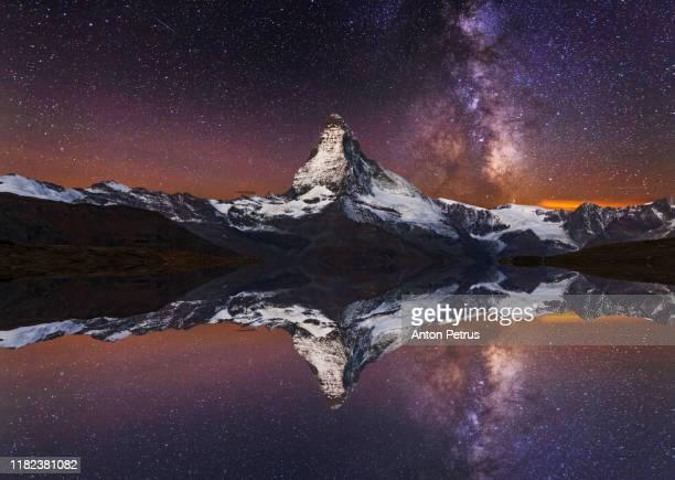 matterhorn peak with milky way at night reflected in stellisee lake in zermatt, switzerland. - weltraum und astronomie stock-fotos und bilder