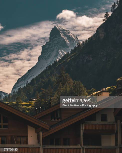 matterhorn peaking through the mountain chalets of zermatt. - pinnacle peak stock-fotos und bilder