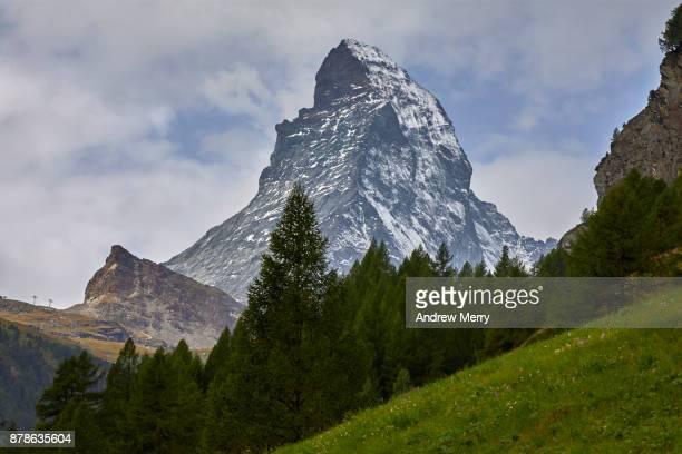 Matterhorn snow-capped with pine forest, green grass and clouds, taken from Zermatt. A classic summer Swiss landscape