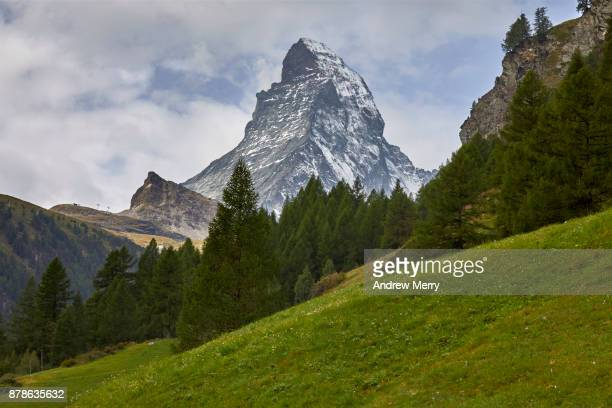 Matterhorn snow-capped with pine forest, green grass and clouds, taken from Zermatt. A classic summer Swiss landscape