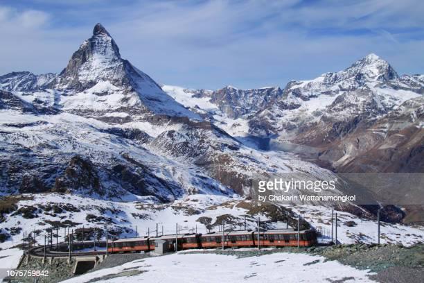 matterhorn (zermatt, switzerland) - the gornergrat train is approaching at gornergrat station with matterhorn and blue sky in the background. - pinnacle peak stock-fotos und bilder