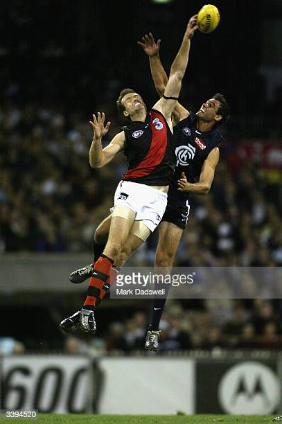 Matthew Allan for the Bombers contests the ruck with Adrian Deluca for the Blues during the round four AFL match between the Carlton Blues and the...