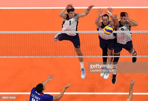 US Matthew Anderson David Lee and Aaron Russell attempt to block the ball during the men's qualifying volleyball match between the USA and France at...