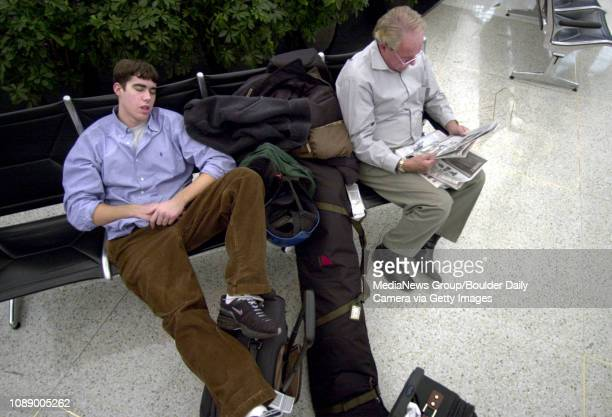Matthew Arentsen takes a nap at Denver International Airport Thursday as his dad Charles reads a newspaper They were waiting for a friend on a...