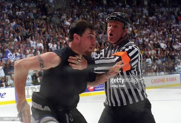 Matthew Barnaby of the Pittsburgh Penguins is held up by referee Terry Gregson against the Toronto Maple Leafs during the 1999 Quarter Finals of the...