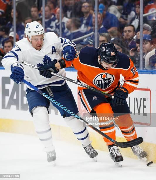 Matthew Benning of the Edmonton Oilers battles against Leo Komarov of the Toronto Maple Leafs at Rogers Place on November 30 2017 in Edmonton Canada