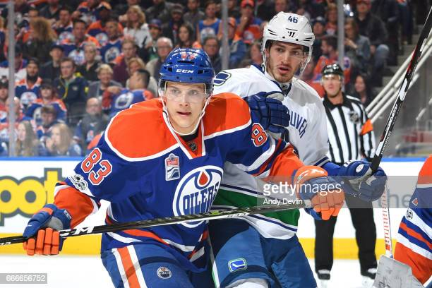 Matthew Benning of the Edmonton Oilers battles for position against Jayson Megna of the Vancouver Canucks on April 9 2017 at Rogers Place in Edmonton...