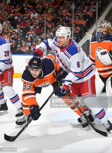 Matthew Benning of the Edmonton Oilers battles for position with Cody McLeod of the New York Rangers on March 3 2018 at Rogers Place in Edmonton...