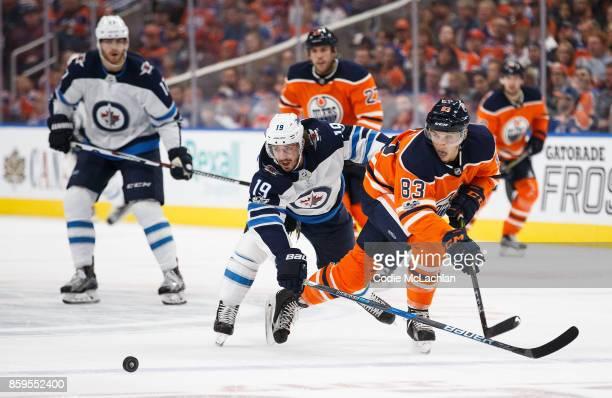 Matthew Benning of the Edmonton Oilers battles Nic Petan of the Winnipeg Jets at Rogers Place on October 9 2017 in Edmonton Canada