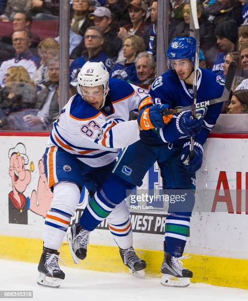 Matthew Benning of the Edmonton Oilers check Jayson Megna of the Vancouver Canucks into the end boards in NHL action on April 8 2017 at Rogers Arena...