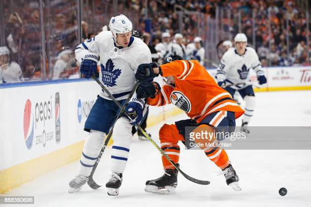Matthew Benning of the Edmonton Oilers defends against Matt Martin of the Toronto Maple Leafs at Rogers Place on November 30 2017 in Edmonton Canada