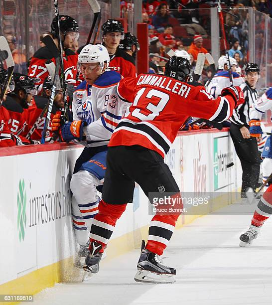 Matthew Benning of the Edmonton Oilers is hit into the boards by Michael Cammalleri of the New Jersey Devils during the second period at the...
