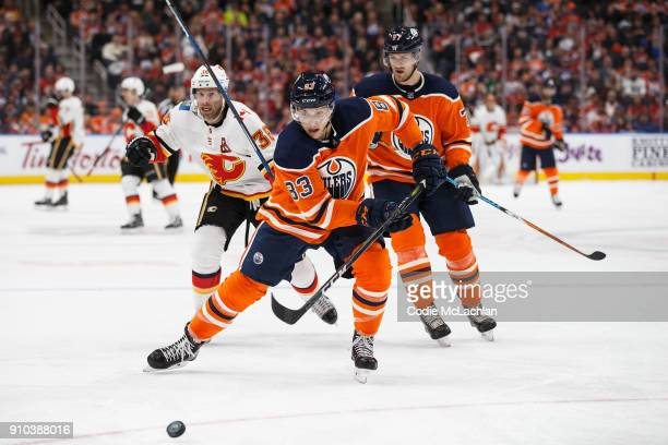 Matthew Benning of the Edmonton Oilers is pursued by Troy Brouwer of the Calgary Flames at Rogers Place on January 25 2018 in Edmonton Canada