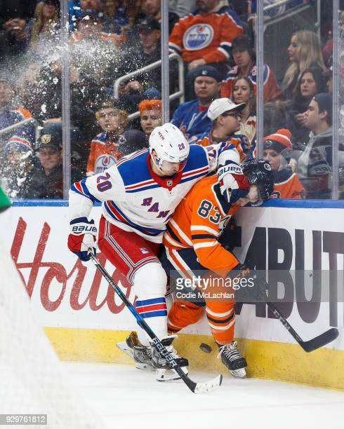 Matthew Benning of the Edmonton Oilers is taken into the boards by Chris Kreider of the New York Rangers at Rogers Place on March 3 2018 in Edmonton...