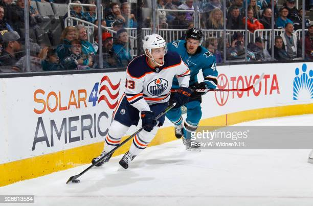 Matthew Benning of the Edmonton Oilers skates with the puck against Tomas Hertl of the San Jose Sharks at SAP Center on February 27 2018 in San Jose...