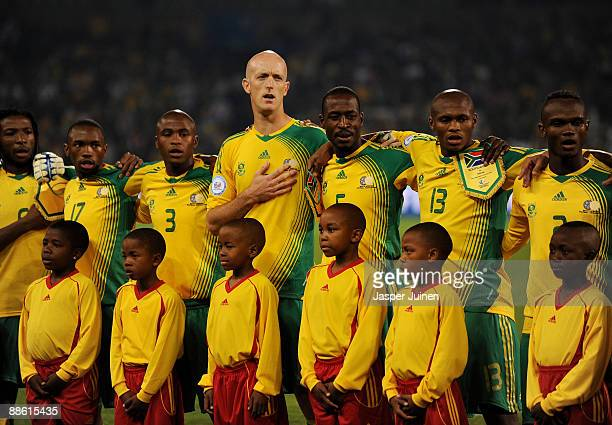 Matthew Booth of South Africa stands with his teammates listening to his countries national anthem prior to the FIFA Confederations Cup match between...