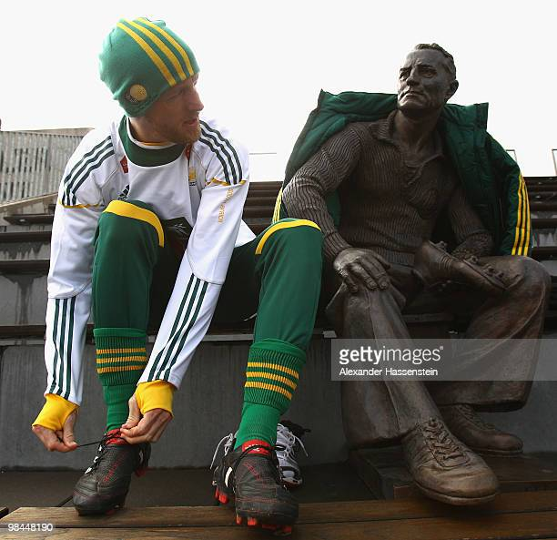 Matthew Booth of the South African national football team sits next to a statue of Adi Dassler founder of adidas company prior to training session of...