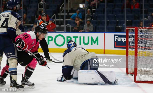 Matthew Boucher of the Quebec Remparts scores a goal against Evan Fitzpatrick of the Sherbrooke Phoenix in overtime during their QMJHL hockey game at...