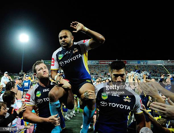 Matthew Bowen of the Cowboys is chaired from the ground by Gavin Cooper and James Tamou at the end of the round 26 NRL match between the North...