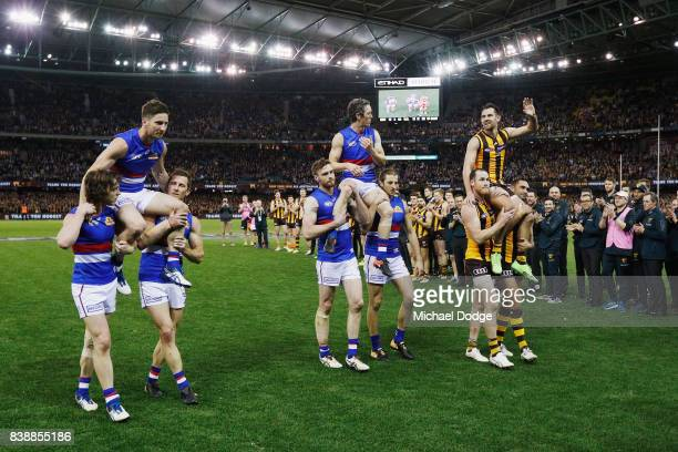 Matthew Boyd and Robert Murphy of the Bulldogs get carried off with Luke Hodge of the Hawks for their retirement match during round 23 AFL match...