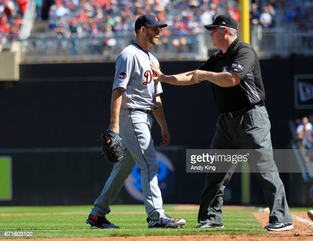 Matthew Boyd of the Detroit Tigers is held back by first base umpire Mike Everitt in the fifth inning after Miguel Sano of the Minnesota Twins...