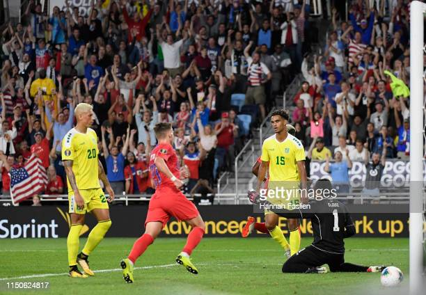 Matthew Briggs Terence Vancooten and goaltender Akel Clarke of Guyana react to a goal by the United States during the first half of the CONCACAF Gold...