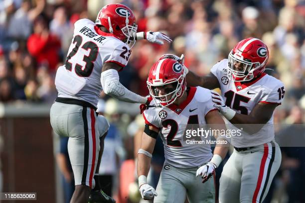 Matthew Brown, Mark Webb, and Trezmen Marshall of the Georgia Bulldogs react to a defensive play during the second half of the game against the...