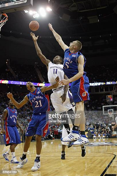 Matthew BryanAmaning of the Washington Huskies puts a shot up against Markieff Morris and Cole Aldrich of the Kansas Jayhawks during the CBE Classic...