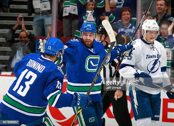 Matthew Carle of the Tampa Bay Lightning looks on dejected as Chris Higgins of the Vancouver Canucks celebrates his goal with teammate Nick Bonino...