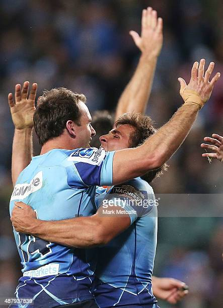 Matthew Carraro of the Waratahs celebrates with team mate Nick Phipps after scoring a try during the round 12 Super Rugby match between the Waratahs...