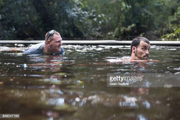 Matthew Cercy, left and Corey Rivera take a swim in flood waters on Thunder Rd. Caused by Hurricane Irma September 12, 2017 in Middleburg, Florida,...