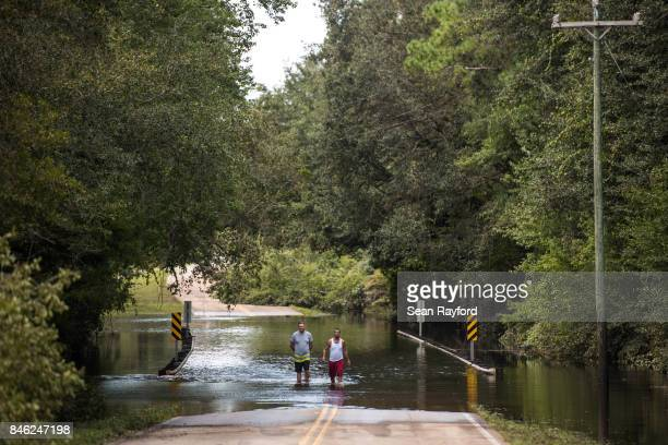 Matthew Cercy, left and Corey Rivera walk through flood waters caused by Hurricane Irma September 12, 2017 in Middleburg, Florida, United States. The...