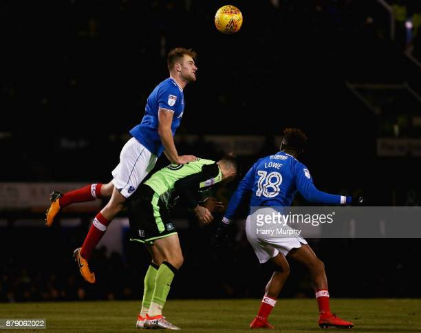 Matthew Clarke of Portsmouth heads the ball clear under pressure from Sonny Bradley of Plymouth Argyle during the Sky Bet League One match between...