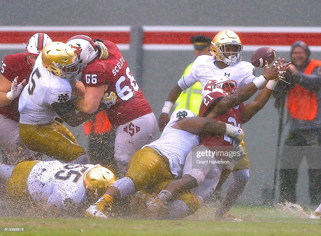 Matthew Dayes #21 of the North Carolina State Wolfpack loses the ball as he is hit by the Notre Dame Fighting Irish defense during the game at Carter Finley Stadium on October 8, 2016 in Raleigh, North Carolina. North Carolina State won 10-3.